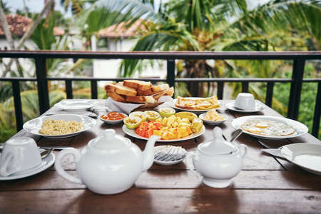 Breakfast ready to eat. Eggs, tropical fruit, toasts and  tea pot on wooden table against palm tree.