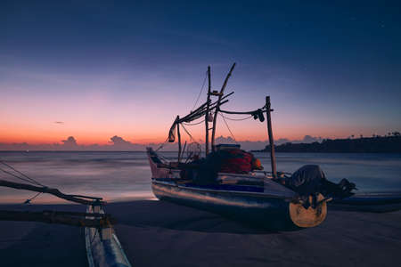Seascape at colorful dawn. Fishing boat on sand beach near Tangalle in Sri Lanka