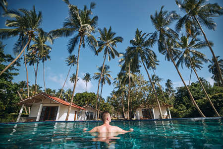 Relaxation in swimming pool in the middle of coconut palm trees. Young man resting in water against bungalows of tourist resort.