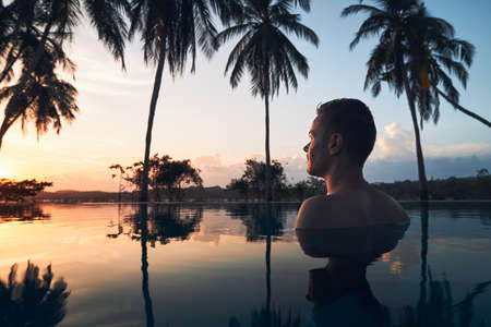 Young man watching sunset from swimming pool in the middle of coconut palm trees. 写真素材