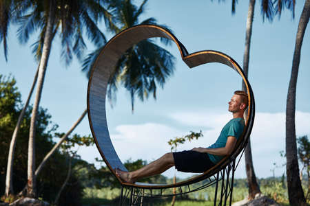 Relaxation in tropical paradise. Young man sitting in wooden heart against palm trees and tropical landscape.