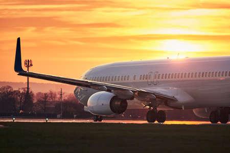 Vliegtuig voor het opstijgen op de baan. Verkeer op luchthaven tegen hemel tijdens kleurrijke zonsondergang.