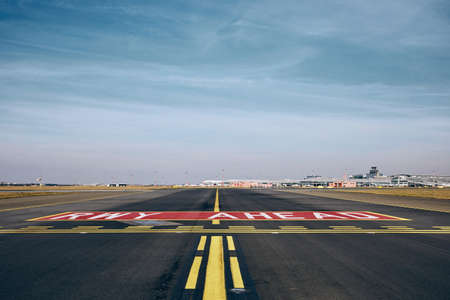 Prague, Czech Repiblic - March 29, 2019: Marking on taxiway before crossing with runway against terminal building Vaclav Havel Airport Prague in Czech Republic on March 29, 2019. 報道画像
