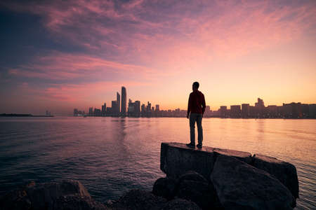 Young man standing on seashore and watching colorful sunrise. Sea and urban skyline Abu Dhabi, United Arab Emirates.
