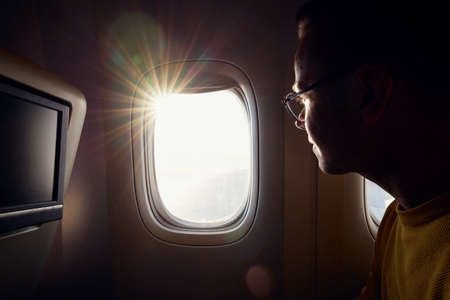 Young man with eyeglasses looking through airplane window during sunny day. 写真素材