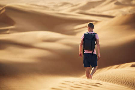 Desert adventure. Young man with backpack walking on sand dune. Abu Dhabi, United Arab Emirates 写真素材