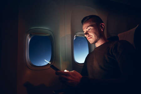 Young man using mobile phone in airplane. Internet connection during flight. 写真素材
