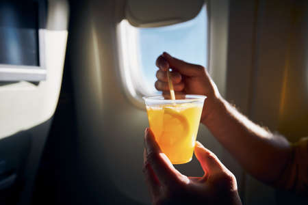 Dring during flight. Man holding cocktail against airplane window.