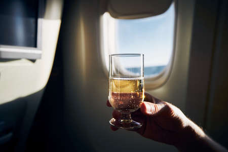 Dring during flight. Man holding glass of sparkling wine against airplane window.