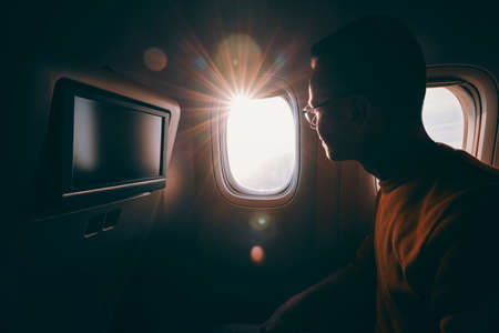 Travel by airplane during sunny day. Young man with eyeglasses looking through window.  写真素材