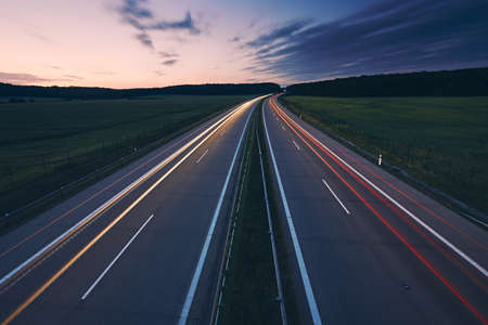 Light trails of cars. Traffic on highway in the middle of fields at beuatiful dawn.