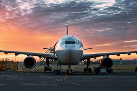 Vorderansicht des Flugzeugs während der Wartung gegen stimmungsvollen Sonnenaufgang. Standard-Bild