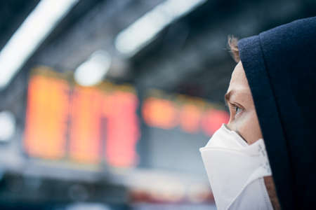 Man wearing face mask against airport departure board. Themes coronavirus, canceled flights and personal protection. 免版税图像 - 143171141
