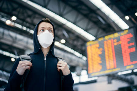 Man wearing face mask against airport departure board. Themes coronavirus, canceled flights and personal protection.