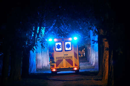 Rear view of ambulance of emergency medical service against dark alley. Themes rescue, hope and health care.