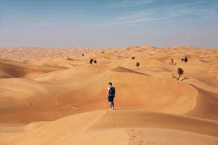 Young man standing on sand dune in the middle of desert. Abu Dhabi, United Arab Emirates Reklamní fotografie