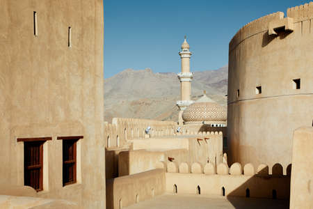 View between watchtowers of historic fort to mosque. Nizwa, Sultanate of Oman. Reklamní fotografie