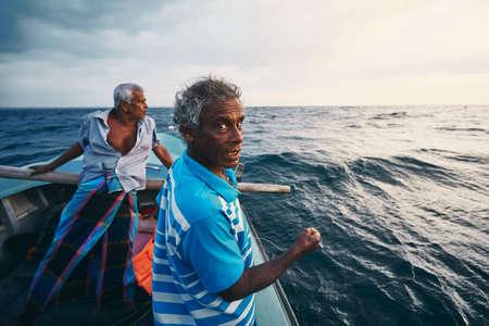 Hard work on sea. Two fishermen on fishing boat near coastline of Sri Lanka.