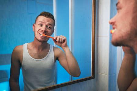 Morning hygiene routine. Man brushing teeth and looking in mirror of home bathroom.