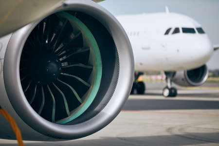 Jet engine of commercial airplane against traffic at airport. Stockfoto