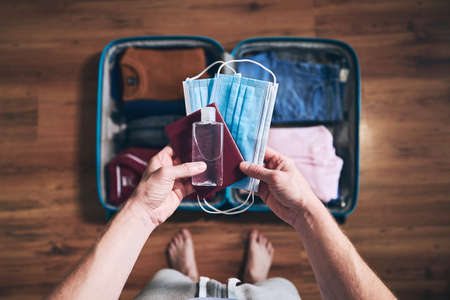 Preparing for travel in new normal. Man packing passport, face masks and hand sanitizer. Themes personal protection and flight rules during coronavirus pandemic. Stockfoto