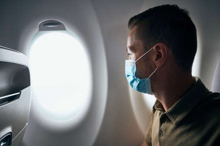 Man wearing face mask inside airplane during flight. Themes new normal, coronavirus and personal protection.