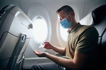 Man wearing face mask and using hand sanitizer inside airplane during flight. Themes new normal, coronavirus and personal protection. Stockfoto