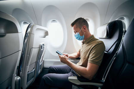 Man wearing face mask and using phone inside airplane during flight. Themes new normal, coronavirus and personal protection. Stockfoto