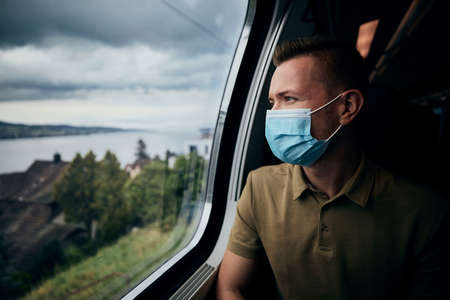 Man wearing face mask inside train. Themes new normal, coronavirus and personal protection in public transportation. Stockfoto