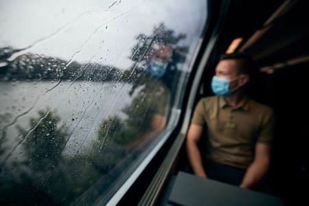 Man wearing face mask inside train in rainy day. Selective focus on raindrops on window. Stockfoto