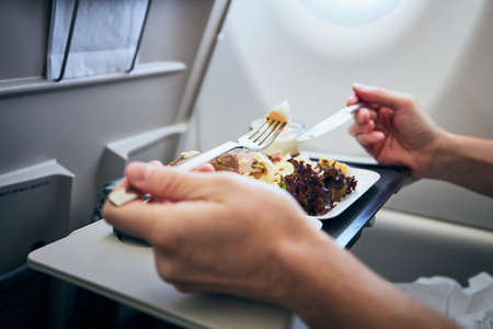 Man eating airline meal served on seat tables during flight. Stockfoto