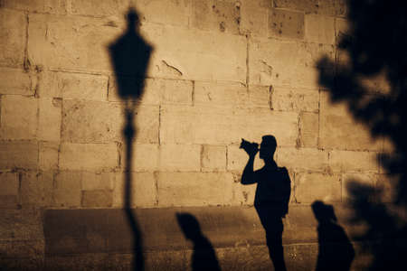 Shadow of photographer on stone wall. Young man photographing of old street at sunset. Zurich, Switzerland.