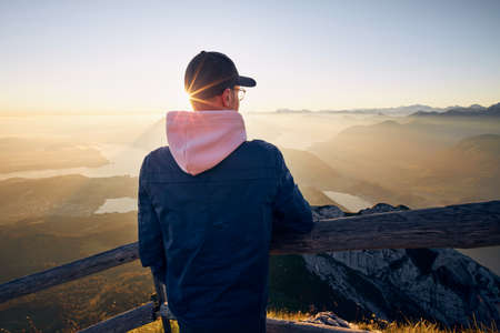 Hiker looking at mountain range at sunrise. View from Mount Pilatus, Lucerne, Switzerland