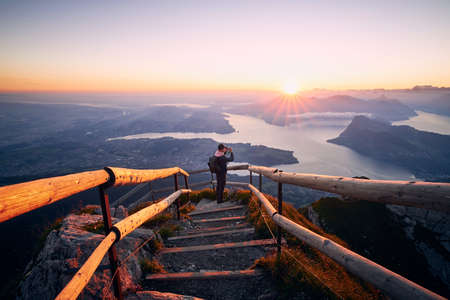Man photographing landscape with lake and mountains at beautiful sunrise. View from Mount Pilatus, Lucerne, Switzerland