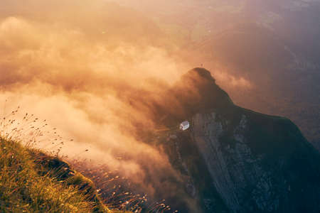 Swiss landscape at beautiful sunset. Chapel on mountain in the middle of clouds. View from Mount Pilatus, Lucerne, Switzerland