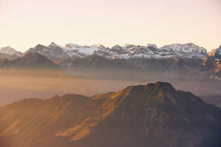 Panorama of snowcapped mountain range at beautiful sunrise. View from Mount Pilatus, Lucerne, Switzerland.