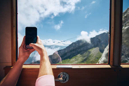 View from window of cogwheel train. Man photographing mountains above cloud in Switzerland.