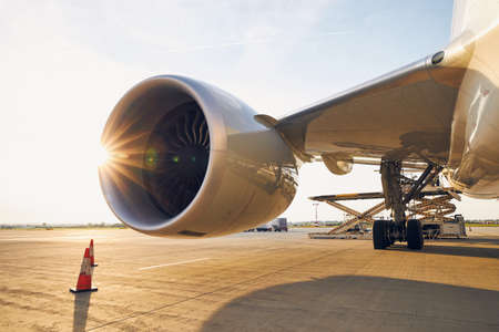 Busy airport at sunset. Large jet engine against loading of cargo containers to airplane. Stockfoto