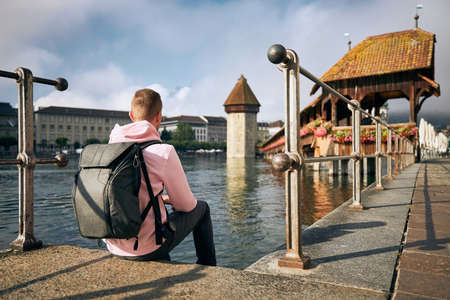 Young man sitting on waterfront and looking at Chapel Bridge in Lucerne, Switzerland. Stockfoto