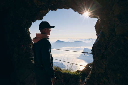 Man inside cave in Mount Pilatus looking at beuatiful landscape of Swiss Alps. Lucerne, Switzerland.