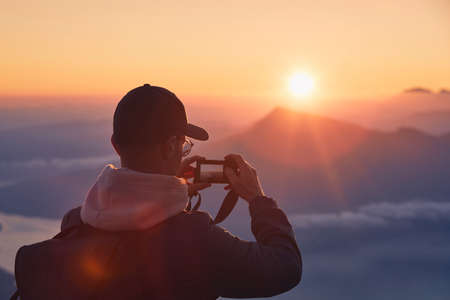 Young man on top of mountain photographing sun under horizon. Lucerne, Switzerland. Stockfoto