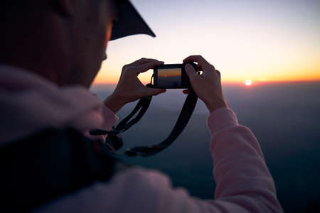 Young man holding camera and photographing sun under horizon.