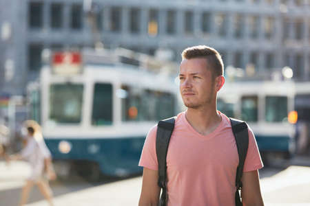 Young man walking on busy city street against tram station. Zurich, Switzerland Stockfoto