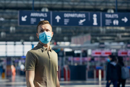 Man wearing face mask against airport check-in counter. Themes travel in new normal, coronavirus and personal protection. Stockfoto