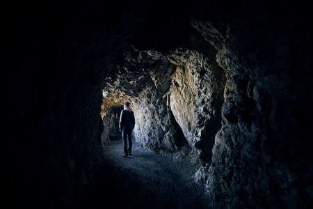Young man is looking into light at the end of the tunnel. Young hiker walking  through tunnel in rock.