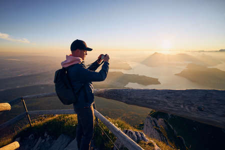 Young man photographing landscape with lake and mountains at beautiful sunrise. View from Mount Pilatus, Lucerne, Switzerland