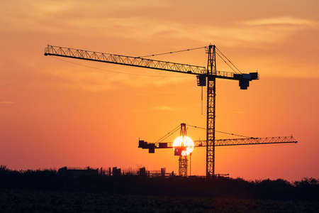 Building activity on contruction site. Silhouettes of cranes against sun. Stockfoto