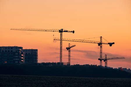 Building activity on contruction site. Silhouettes of cranes against golden sky.