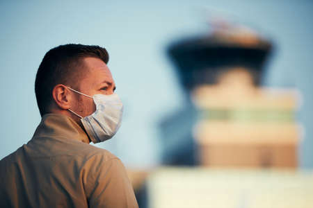 Man wearing face mask at airport. Themes travel in new normal, coronavirus and personal protection.