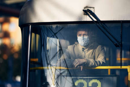 Man wearing face mask and looking from window of tram. Themes public transportation in new normal, coronavirus and personal protection.